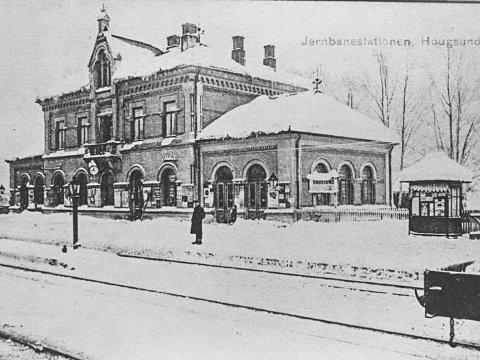 HISTORIEBILDET:  Her ser du Hougsund stasjon en vinterdag i en svunnen tid. Bildet skal være tatt mellom 1900 og 1920, men kanskje noen av våre lesere vet mer om når bildet er tatt og hvem personen på bildet er? Ved siden av stasjonen, ser vi  bladkiosken som var et fast innslag ved mange stasjoner på den tiden. Bildet er hentet fra arkivet til Øvre Eiker bibliotek/Eiker arkiv.                 Har du gamle bilder fra Midtfylket, som du vil dele med Bygdepostens lesere, hører vi gjerne fra deg. gamle bilder og tekst kan også sendes som e-post til: redaksjonen@bygdeposten.no.