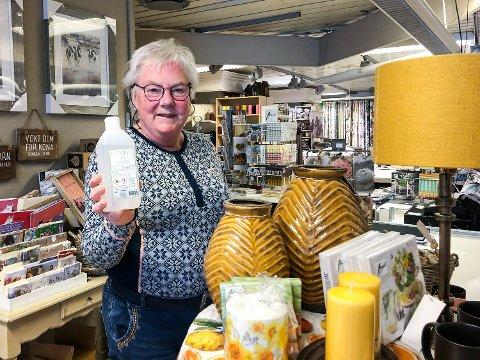 HOLDER ÅPENT: Berit Gravermoen ved Cehita i Vikersundgata holder butikken åpen for kundene så lenge hun har lov. – Jeg er nøye med renholdet, sier hun og viser fram flaska med desinfeksjons-sprit.