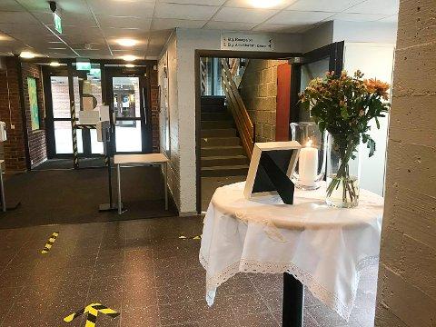 MINNES: Det er satt opp et bord med lys, blomster og et bilde av 17-åringen i gangen innenfor hovedinngangen på Buskerud videregående skole.