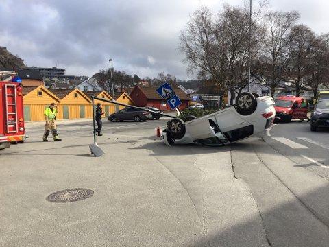 Bilen ble liggende på hodet like ved et av byens mest trafikkerte fotgjengerfelt. En lyktestolpe er nedkjørt.