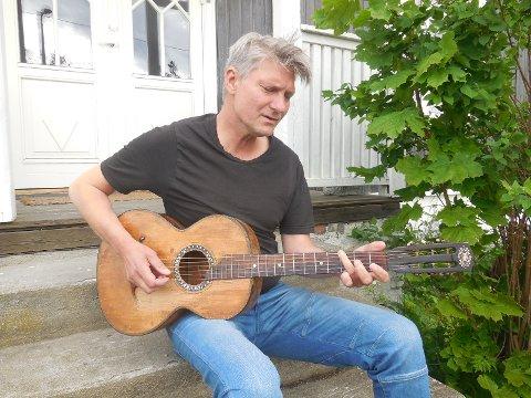 BILLIG GITAR: Johny Aasgard med gitaren han kjøpte på loppemarked for 200 kroner, og skaper magi med, på trappa hjemme i Vestfossen.