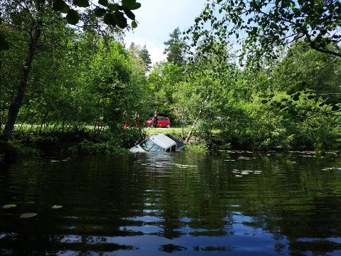 Her ligger bilen i vannkanten. Personene i bilen skal ifølge politiet ha stukket fra stedet.