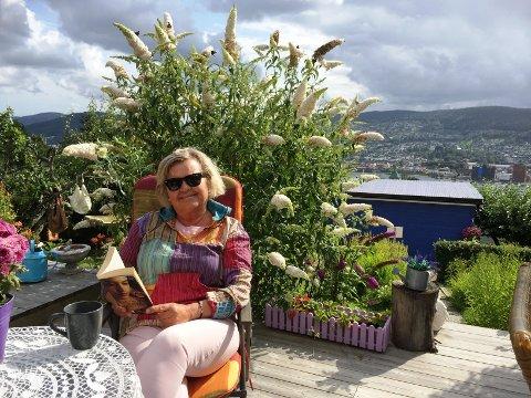 Eva Ed sitter ofte på terrasen, og koser seg med bok og kaffe. Legg merke til alle sommerfuglene i busken bak. Det er en sommerfuglbusk som tiltrekker seg sommerfugler.