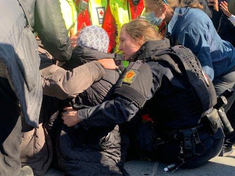 HJELP: En kvinne besvimte under opptøyene på Strømsø lørdag ettermiddag. Da tok politiførstebetjent Kathrin Dale (t.h.) av seg gassmasken og hjelmen for å hjelpe.