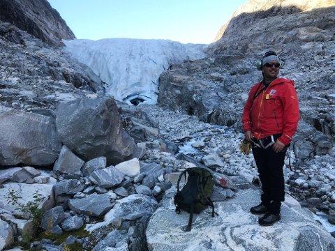 SMELTAR: Jostein Aasen i NVE framfor Stigaholtbreen. Brefronten har smelta 117 meter tilbake dei siste ti åra. Måling på steinen viser punktet som brefronten målast fra. Ålfotbreen i Flora og Bremanger har ein endå dystrare statistikk.
