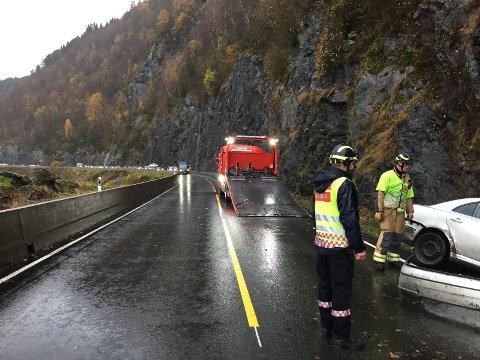Bilbergar gjer seg klar til å fjerne personbilen som har hamna i fjellveggen.