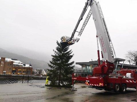 VINDEN TOK TREET: Her prøver Førde brann og redning å fikse juleetreet etter at vinden knakk av toppen av juletreet.