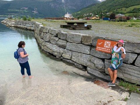 Posering ved skiltet som fortel at ein er på Norges minste og kaldaste strand.