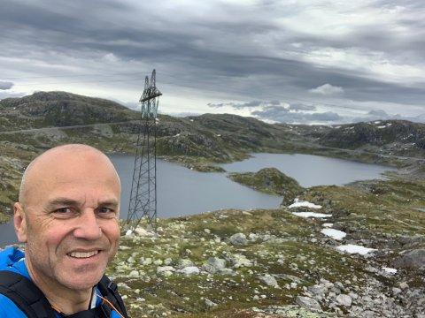 INVESTERING: Erik Espeset er grunneigar i Viksdalen. Han spør om det er lurt å seie nei til investeringa som vindkraftselskapa tilbyr. Her er han med ei Statnett-mast og Steinbrua i bakgrunnen.