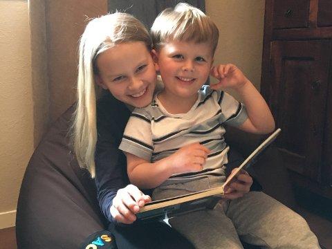 HYGGESTUND: Mia Trælnes (11) og Joakim Trælnes (3) les bok saman i saccosekken. – At eldre søsken les til yngre er jo ein vinn-vinn-situasjon for alle partar, seier Nathalie Trælnes.