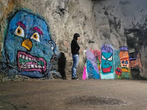 """GATEKUNSTNAR: Kunstnaren """"Le Che"""" foran kunstverket. Han har prøvd å dekkje over dei verste teikningane, men ein kan framleis skimte spor. Fjeset til venstre er det nyaste tilskotet til tunnelen."""