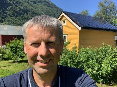 NØGD MED SOLCELLE-STABBURET: På Gåsemyr på Breim har Bjarte Heggedal fått installert solcellepanel på stabburstaket sitt. Her står han og smiler ved bygget. Foto: Bjarte Heggheim.
