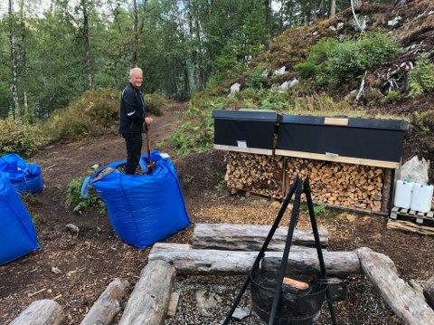 VEDEN LIGG KLAR: Det ligg alltid ved klar ved bålpanna, slik at kven som helst kan fyre opp. Her står Kjell Arvid Stølen på ein av sekkane med grus som er frakta opp med helikopter.
