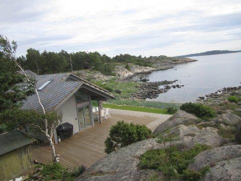 Den omstridte hytta ligger praktfullt ved sjøen i Stangerholmveien på Skjæløy