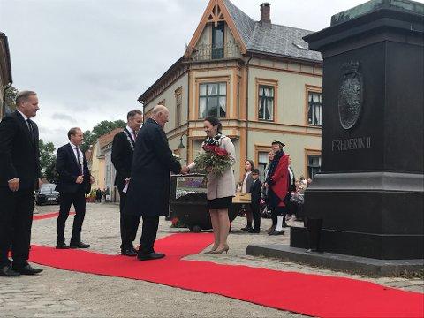 HILSTE PÅ KONGEN: Byjubileumssjef Irene Østbø overrakte blomstene som Kongen la ned ved statuen av Kong Frederik.