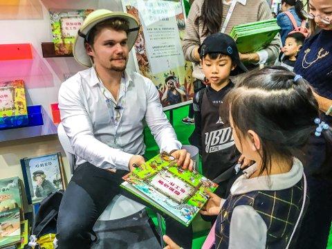Tett trafikk: Haakon Lie måtte signere 150 bøker og en mengde papirlaper under oppholdet i Shanghai. Kineserne ville ha boka hans.
