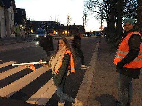 Full kontroll: Arijona Osmani sørger for at fotgjengere kommer seg trygt over veien ved togstasjonen. Ansvarlig for trafikkpatruljen og lærer Gaute Blekken er ute sammen med elevene.