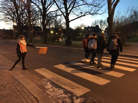 På begge sider: Mens Arijona Osmani står på den andre siden av veien, passer Elisabeth Christiansen (12) på her. Slik får elevene gitt signal til alle som kommer fra ulike kanter, både myke og harde trafikanter.