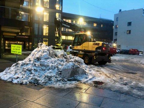SAMLES: Snøen samles først i store hauger rundt i sentrum før den flyttes med lastebiler til Porselenskaia.