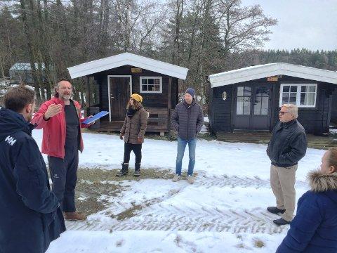 Beach houses: Eivind Simonsen (i rødt) forklarer Fast utvalg for miljø og teknikk om de tre hyttene i bakgrunnen, da utvalget gjennomførte en befaring.