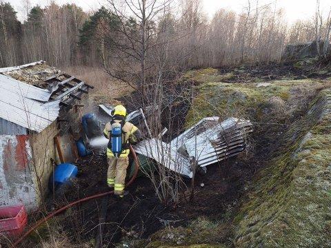 Brannvesenet slokker markbrannen og uthuset.