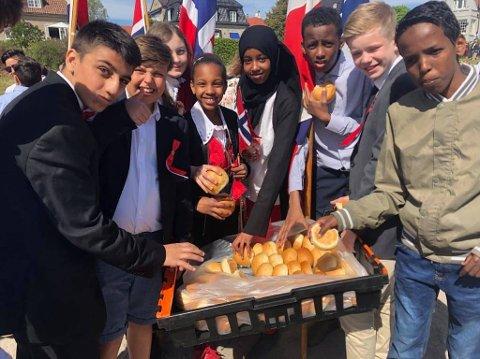 Elever fra Nøkleby skole visste å forsyne seg da det ble budt på boller på Tollbodplassen før barnetoget i formiddag.