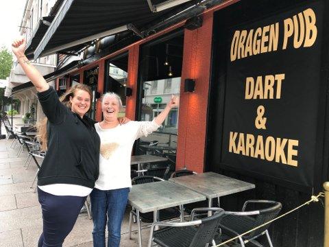 STARLETS: Pernille Holmqvist (t. v.) forteller om medaljedryss for Dragen Pub i karaoke-NM. Her flankeres bartenderen av karaoke-gjest Marianne Larsen.