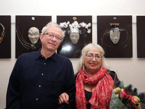Arne Aalberg og hans kone Grethe Anna Larsen foran et utvalg av maskene i deres kunstinstallasjon «Tretten til bords». Deres utstilling henger i kafeen til Østfold kunstsenter.