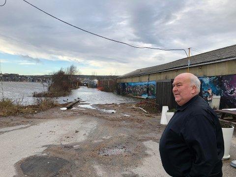 Ulf Berg står her foran lokalene til loppemarkedet Loppeberget på Trosvikstranda. Veien er helt oversvømt av vann.