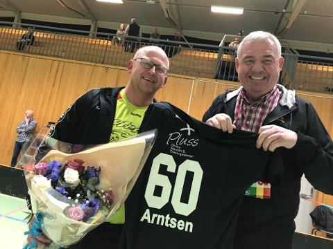 60: Thomas Arntsen fikk både blomster, supporterutstyr og noe å bite i av Sleviks Morten A. Johnsen. Bak duoen er de vanligvis så folksomme tribunene ribbet for alt annet enn kamerafolkene som sto for live-streamingen.