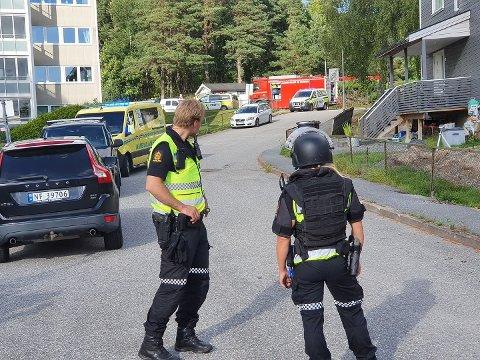 BEVÆPNET: Bevæpnet politi er på plass ved boligblokken i Halden. Foto: Gunnar Paulsen/Halden Arbeiderblad