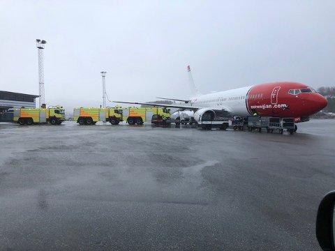 Tre brannbiler på rekke og rad sørget for at passaskjerene kom seg trygt inn i terminalbygningen fra Norwegian-flyet på Harstad/Narvik lufthavn, Evenes.