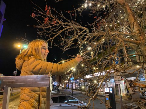 PYNTER TIL JUL:  Sandra Elisabeth Bergvik (17) er en del av russegruppen som monterte lys i trærne oppover Gate 1.