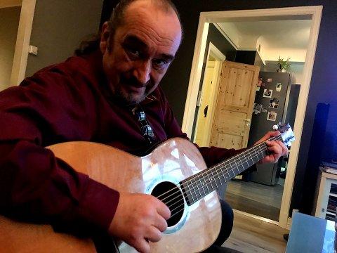 GITARGLAD: Steinar Albrigtsen er glad i gitarer og har mange av sorten hengende på veggen hjemme. Her har han trukket frem det nyeste tilskuddet i familien, en tenorgitar og han viser mer enn gjerne hva den er god for.