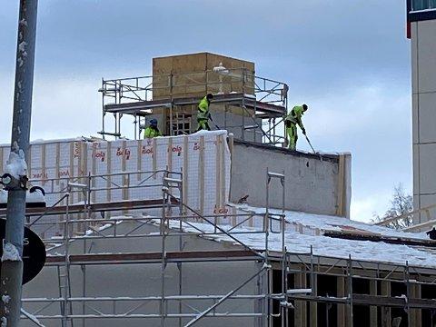 SNØ: Her ser vi arbeiderne stå helt ute på kanten og koster nysnø av taket onsdag morgen.