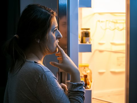 Young woman looking in the refrigerator at late evening