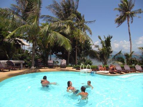 Koh Phangan, Thailand 20100715. Turister nyter livet i et basseng soler seg, svømmer. Grønne palmer, strand og hav i bakgrunnen. Solsenger. Syden, ferie. Foto: Berit Keilen / NTB