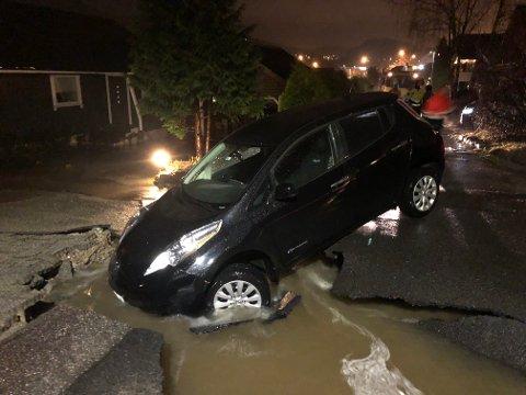 En bil har kjørt nedi et hull gravd ut av store vannmasser på Opstad tirsdag kveld.