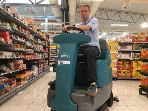 Assisterende butikksjef Morten Tjemsland kjemper mot vannmassene som har trengt seg inn i butikken.