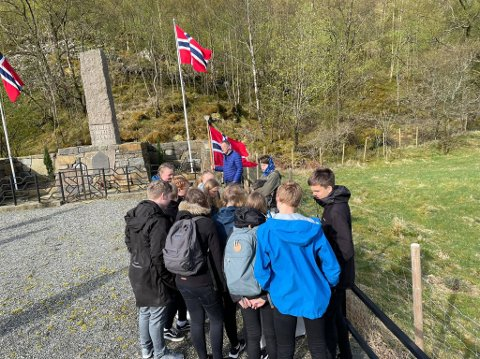 Elever fra Dirdal skule studerer den nye tavlen ved minnestøtten i Dirdal. I bakgrunnen står veteran Ivar Nødland.