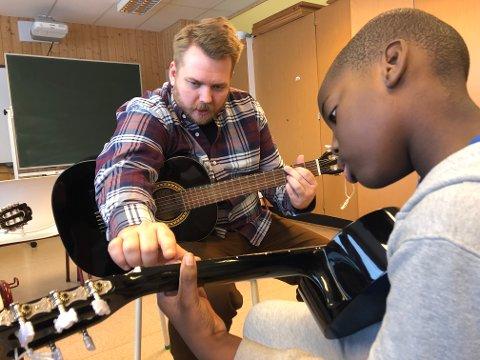 LÆREREN: Henrik Berg Enger er lærer ved siden av å reise landet rundt med Spilloppmaker. Det er stas for elevene når han kan lære bort noe av alt han kan trylle fram på gitaren.