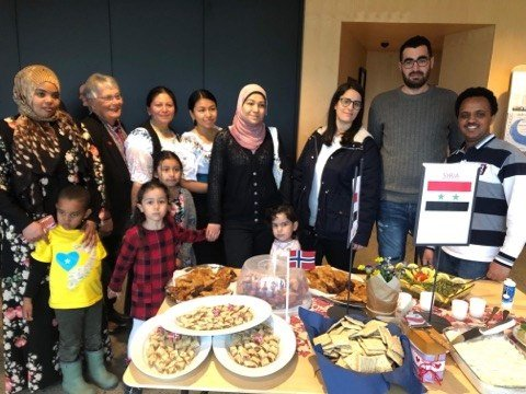 Hana med Anas, biskop Solveig Fiske med Mirna og Maria foran, Blanca, Sayana, Hala, Nermine, Maher og Yacob samlet ved det fristende matbordet.