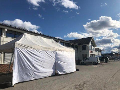 BESKYTTELSE: Det måtte settes opp telt utenfor korona-senteret på Flisa. Folk satt og fotograferte mens andre ble testet av helsepersonell.