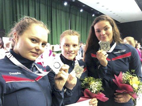 Sølvjentene: Jenny Stene (til ventre), Jeanette Hegg Duestad og Johanna Reksten med sølvmedaljene rundt halsen i Wrocslaw søndag kveld. FOTO: NORGES SKYTTERFORBUND