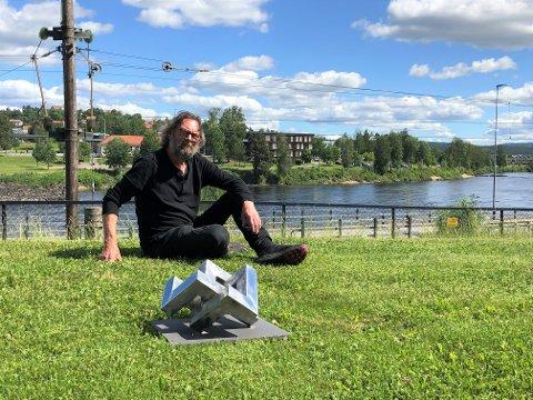 Kunstner Dag Skedsmo fra Kongsvinger vant konkurransen om utsmykking - her ser du han med modellen av den 2,30 x 3.80 meter store skulpturen, som skal plasseres her på elvebakken mellom brua og stasjonen.