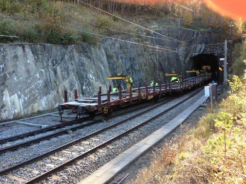 Et arbeidstog har sporet av på Dovrebanen ved Dombås. Toget står inne i en tunnel, og på bildet ser vi de bakerste vognene som står igjen utenfor tunnelen. Jernbaneverket jobber med å få toget på skinner igjen.