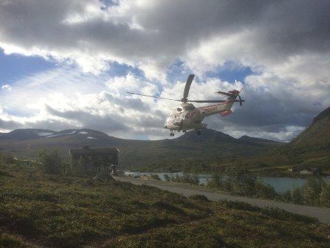 Et helikopter lander ved turisthytta Gjendesheim med en del av turfølget som gikk seg fast ved Besseggen onsdag kveld.  Etter to turer var alle hentet ned.