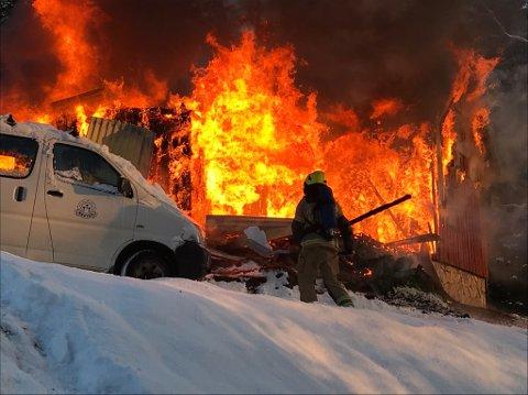 Et bolighus på Rudshøgda brant ned til grunnen fredag formiddag. Brannbilene kom ikke opp den bratte bakken til huset. Det var for glatt. Her måker brannmannskapene snø på en bil for å hindre den i å ta fyr.