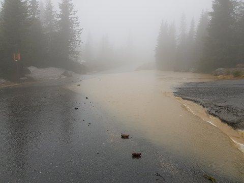 Ved Natrudstilen er det flomvann langt inn i kjørebanen på bilvegen og vanskelig å ta seg fram.
