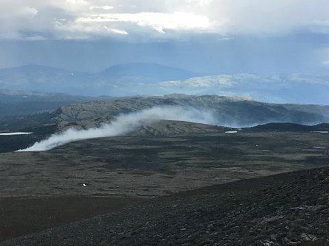 Røyken brer seg torsdag klokken 14.30 som et belte opp fra brannen i Glitterdalen.  Til høyre skimtes hyttebebyggelse på toppen av Tjønnbakken. Bildet er sendt til GD fra et turfølge som befinner seg på Illmannhø i Rondane.